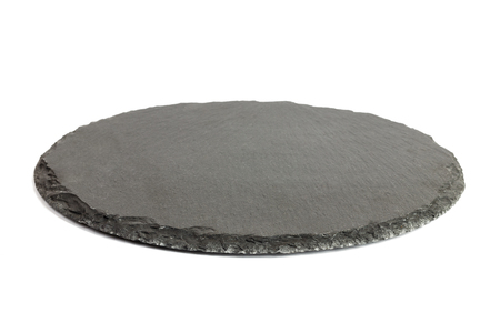 Round rustic black slate stone plate, isolated on white background.