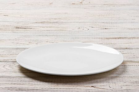 White Round Plate on white wooden table background. Perspective view. Standard-Bild