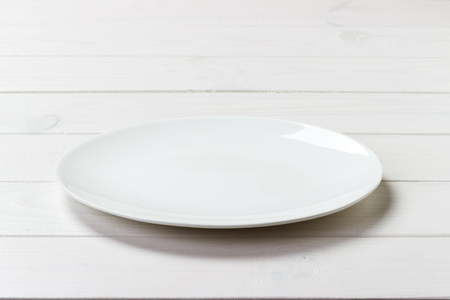 White Round Plate on white wooden table background. Perspective view. Banque d'images