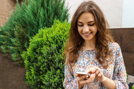 Girl hand holding a smart phone outdoor with a green background. Stock Photo