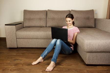 Hermosa chica en ropa casual está usando una computadora portátil y sonriendo mientras está sentado en el piso cerca del sofá en casa.