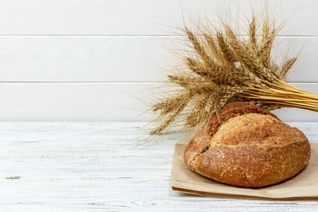 Homemade loaf of wheat bread baked on wooden background.