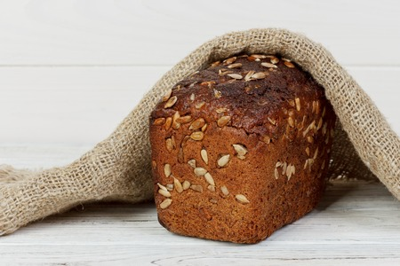 Traditional round rye bread on white wooden table.
