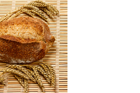 Toasty Organic Loaf of Bread with wheat on wooden plank isolated on white.
