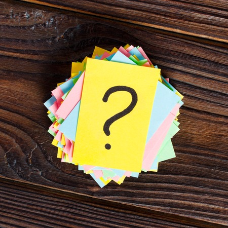 colorful question marks written reminders tickets on wooden background.