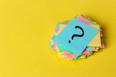 Question mark paper heap on yellow background, concept for confusion.