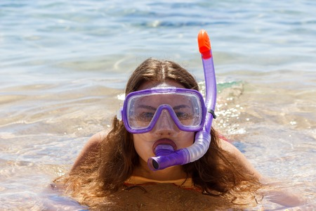 Beach vacation fun woman wearing a mask tube for swimming in ocean water. Close-up portrait of a girl in her travel holidays.