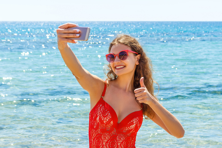 young girl having fun taking smartphone selfie pictures of herself. travel holidays. happy young woman giving hand sign thumbs up on beach.