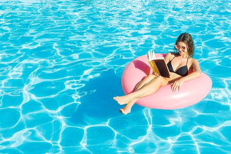 Beautiful woman reading a book on inflatable ring in blue swimming pool. Stock Photo