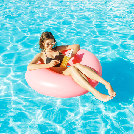 bikini girl with sunglasses relaxed and reading book on pink inflatable pool ring. Banco de Imagens