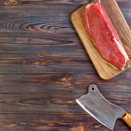 vintage cleaver and raw beef steak on dark wooden background. copy space.
