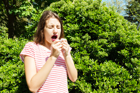 unhappy woman with napkin sneezing in the green park.