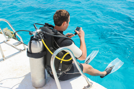 Diver preparing to dive into the ocean from a yacht with his underwater camera.