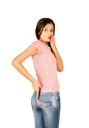 surprised girl shows a finger on the torn jeans isolated on white background. emotional girl isolated on white background. Foto de archivo