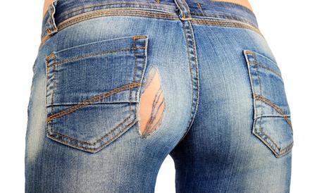 jeans azules con un agujero en el primer plano del Papa, jeans rotos o rotos en la niña. aislado. Foto de archivo