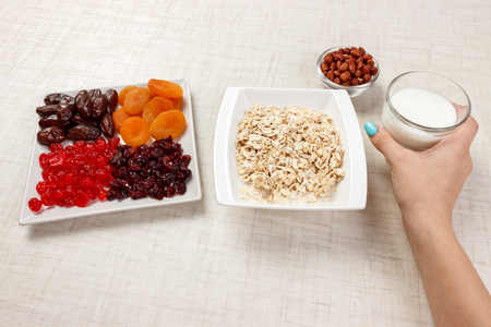 The girl took milk to pour it into oatmeal. Useful and healthy breakfast. White background.