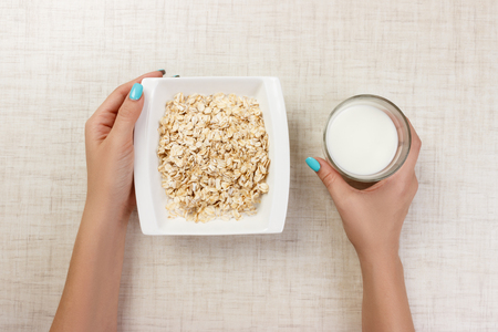 The girl took milk to pour it into oatmeal. Useful and healthy breakfast. light background.
