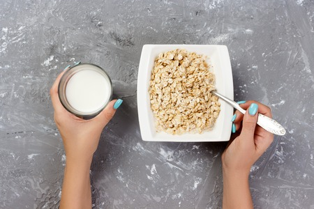 The girl took milk to pour it into oatmeal. Useful and healthy breakfast on a gray background, top view.