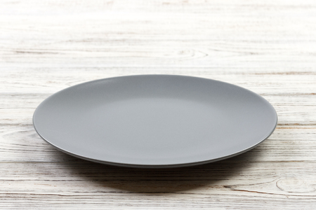 Perspective view. Empty Gray round plate on wooden background. Фото со стока