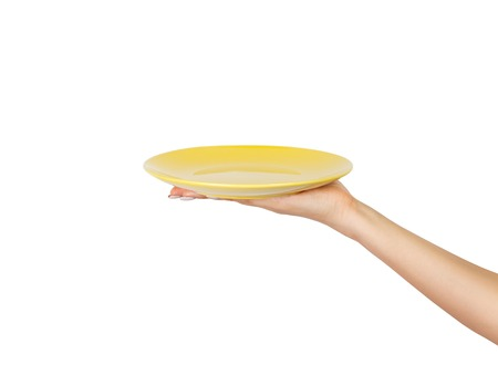 Blank empty round yellow plate in female hand. perspective view, isolated on white background. Foto de archivo