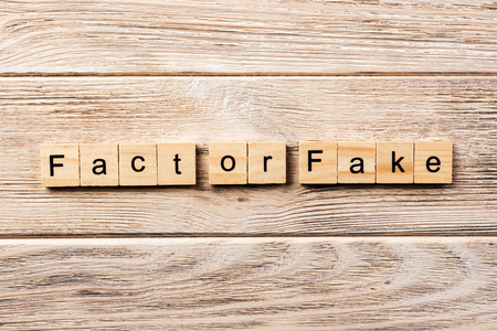 fact or fake word written on wood block. fact or fake text on table, concept.