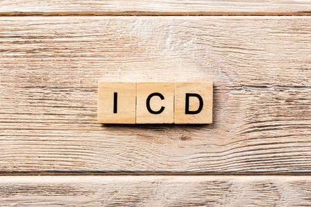 icd word written on wood block. icd text on table, concept.
