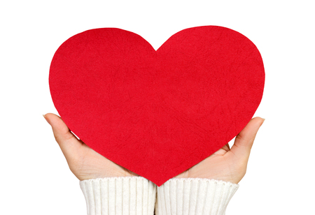 A close up of a female hand holding a red paper heart with copy space. Love and romance concept. Isolated on a white background.