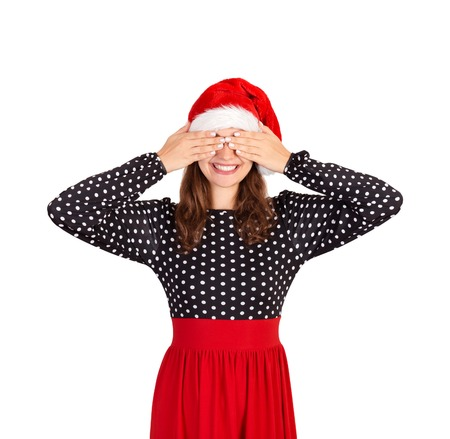 woman in dress closes eyes with her hands. emotional girl in santa claus christmas hat isolated on white background. holiday concept. Stock Photo