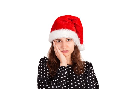 Displeased fed up attractive woman in dress leaning head on palm. sulking from displeasure. emotional girl in santa claus christmas hat isolated on white background. holiday concept.