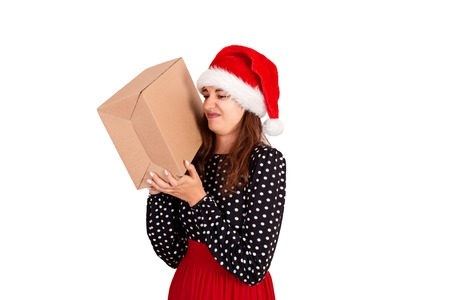 pretty girl in santa hat is not happy and is disgusted her gift. isolated on white background. holidays concept.