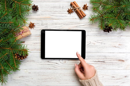 Christmas online shopping. Female hand touch screen of tablet, top view on wooden bakground, copy space. Winter holidays sales background.