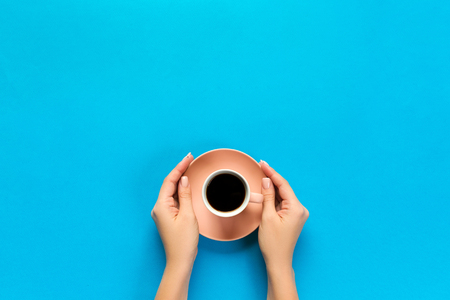 female arms hold mug of coffee on blue background. top view with cope space.