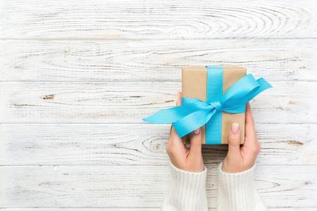 Le mani della donna danno il regalo di San Valentino avvolto o altro regalo fatto a mano di festa in carta con il nastro blu. Scatola attuale, decorazione del regalo sul tavolo di legno bianco, vista dall'alto con spazio per le copie.