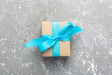 Gift box with blue ribbon and bow on a gray cement background. top view. Stock Photo