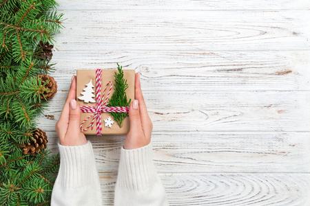 Confezione regalo di Natale avvolta in carta riciclata, con fiocco in nastro, con nastro su fondo rustico. Concetto di vacanza.