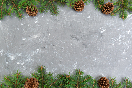 Christmas gray cement wooden background with fir tree frame and cones copy space. top view empty space for your design.