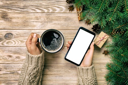 Female hands holding modern smartphone with mosk up and mug of coffee on wooden vintage table with christmas decoration. top view.