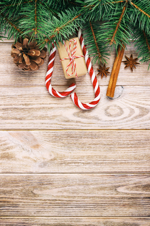 Christmas gift, candy canes and snowflakes on a wooden rustic vintage background.