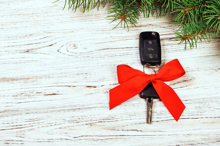 gift for christmas car keys. Close-up view of car keys with red bow as present on wooden rustic vintage background.