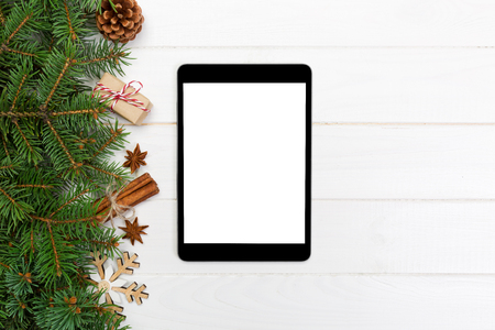 Digital tablet mock up with rustic Christmas wooden background decorations for app presentation. top view with copy space.