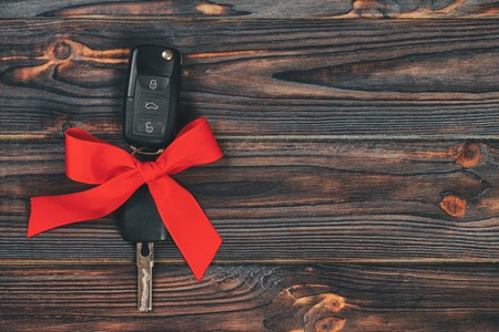 Close-up view of car keys with red bow as present on wooden vintage background.