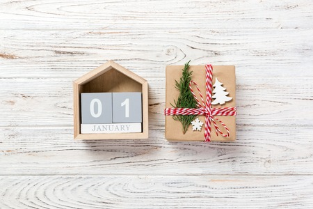 Christmas calendar 1 january. Christmas gift, fir branches on wooden white background. Copy space, top view.