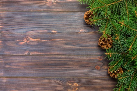 Christmas gray wooden background with fir tree frame and cones copy space. top view empty space for your design.