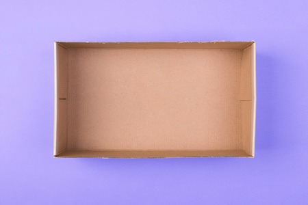 empty cardboard paper box on purple background. delivery concept, top view. 스톡 콘텐츠