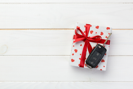 Valentine or other holiday handmade present in paper with red hearts, car keys and gifts box in holiday wrapper. box gift on white wooden table top view with copy space, empty space for design. Reklamní fotografie