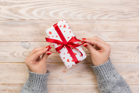Woman hands give wrapped valentine or other holiday handmade present in paper with red ribbon. Present box, red heart decoration of gift on wooden table, top view with copy space for you design. Stock Photo