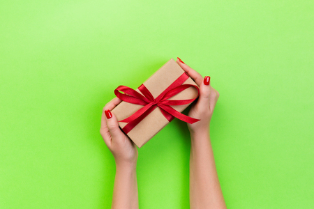 Woman hands give wrapped valentine or other holiday handmade present in paper with red ribbon. Present box, decoration of gift on green table, top view with copy space. Stock Photo