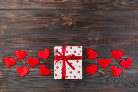 Valentine or other holiday handmade present in paper with red hearts and gifts box in holiday wrapper. Present box of gift on dark wooden table top view with copy space, empty space for design.