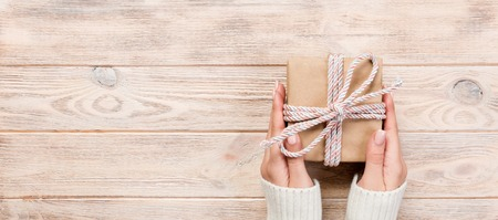 Woman hands give wrapped valentine or other holiday handmade present in paper with blue ribbon. Present box, decoration of gift on white wooden table, Top view banner with copy space for you design. Archivio Fotografico - 115080389