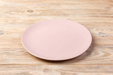 Perspective view. Empty rose matte dish for dinner on orange wooden background. Фото со стока